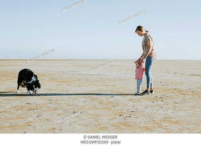 Netherlands, Schiermonnikoog, mother walking with little daughter on the beach at low tide