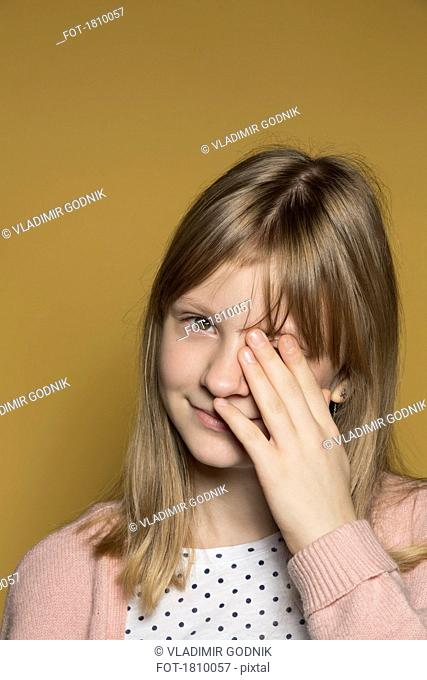 Portrait smiling tween girl covering eye with hand