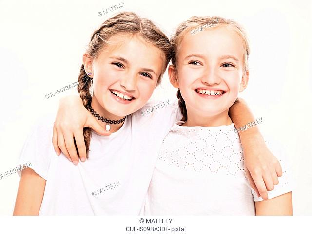 Studio portrait of two girls with arms around each other, head and shoulders