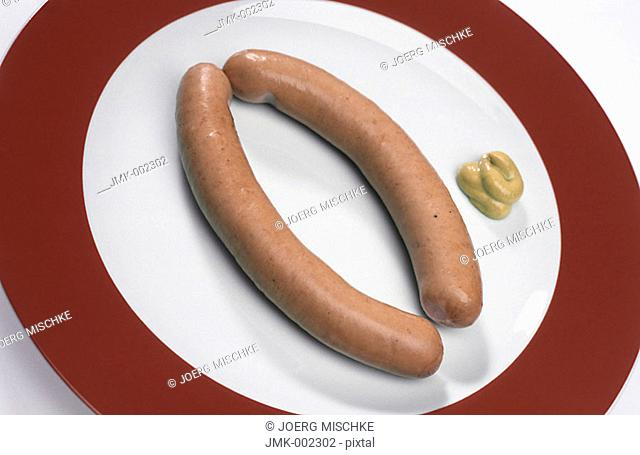 Two sausages on a plate with mustard