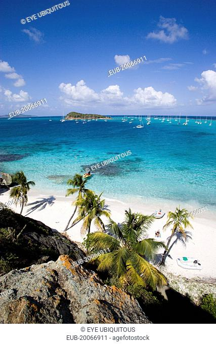 View over the beach of Jamesby Island and moored yachts towards Canouan on the horizon
