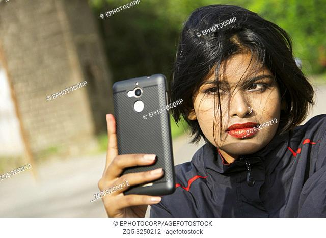 Close-up of young Indian girl with short hair wearing nose ring taking selfie, Pune