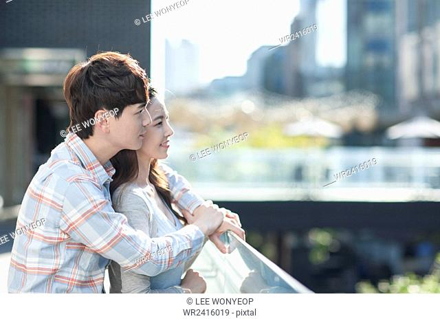 Couple looking out outside together in hug