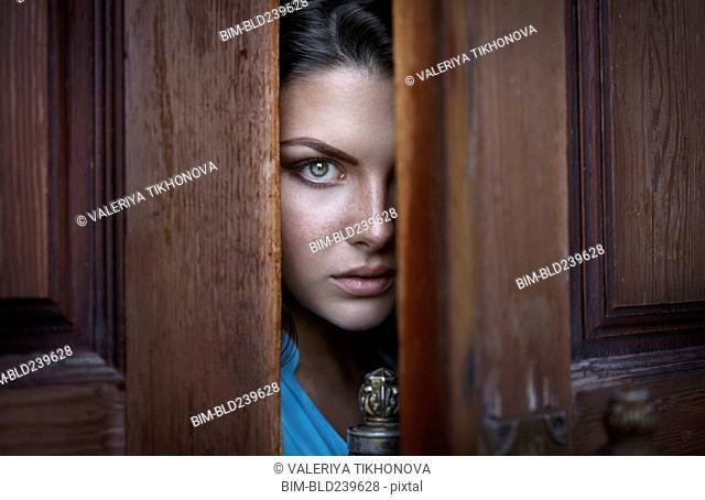 Caucasian woman peeking in doorway