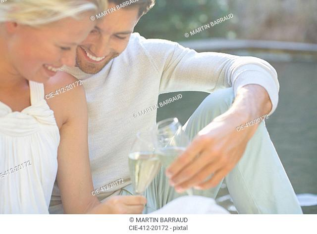Couple toasting each other with champagne outdoors