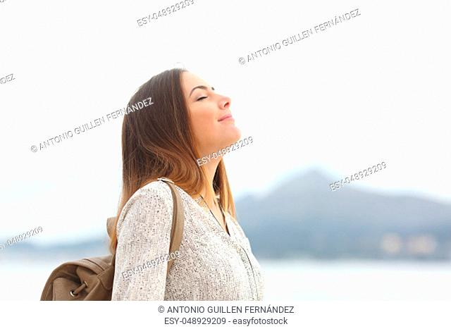 Side view portrait of a happy woman on the beach breathing fresh air