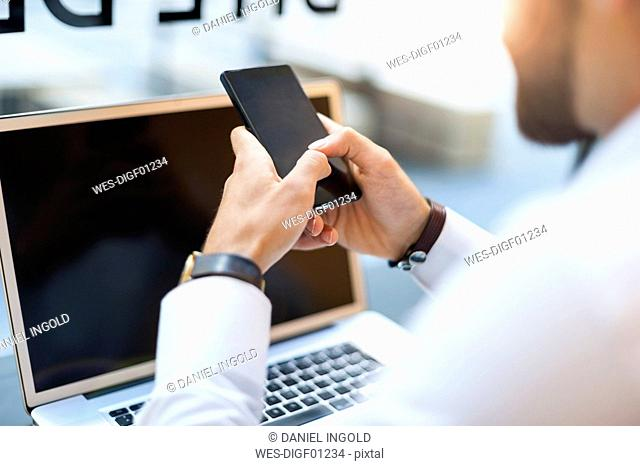 Close-up of businessman with cell phone and laptop in a cafe