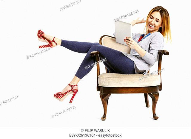Young woman sitting on a chair with pulled legs relaxing and watching funny news on tablet