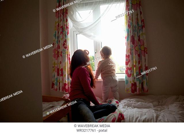 Mother with her baby girl looking through window