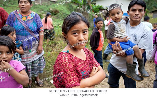 Chahal, Guatemala, a maya tribe in the jngle of Guatemala. A curious father is watching his daughter and carrying his son