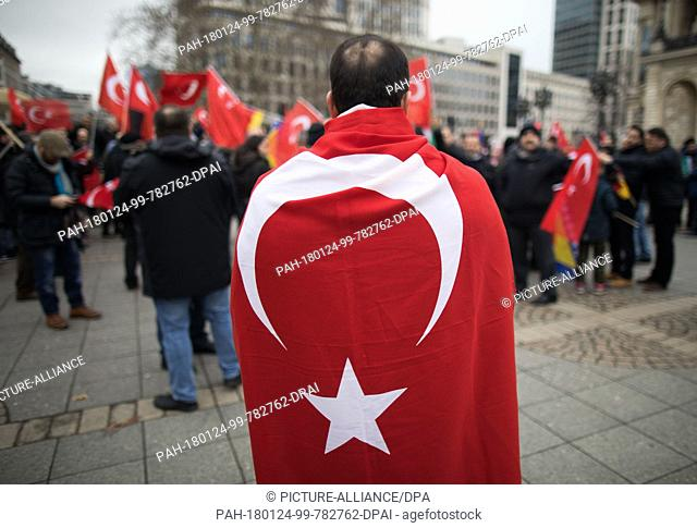 A protester wrapped in a Turkish flag attending a rally in front of the Alte Oper in Frankfurt am Main, Germany, 24 January 2018