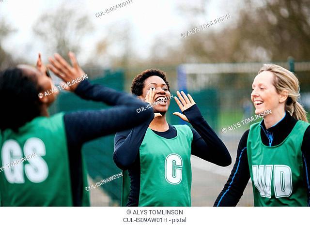 Adult female netball team celebrating win on netball court