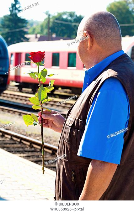 Mature vital elderly couple at the train station.Traveling on vacation