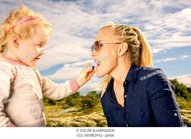 Young girl feeding mother blueberry