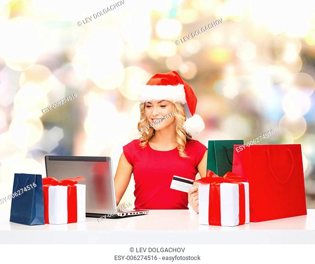 christmas, holidays, technology and shopping concept - smiling woman in santa helper hat with gifts, credit card and laptop computer over lights background