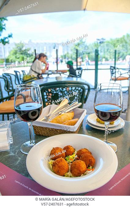 Croquettes serving and two glasses of red wine in a terrace. Oriente Square, Madrid, Spain