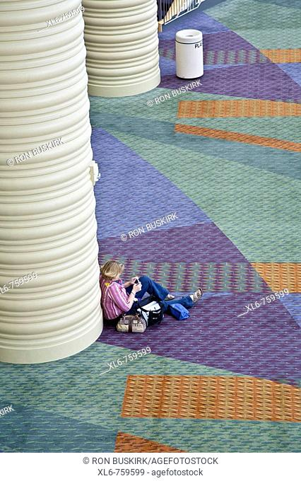 Looking down on woman alone leaning on column in large conference all