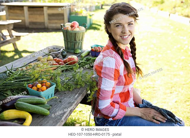 Woman sitting next to harvested fruit and vegetables