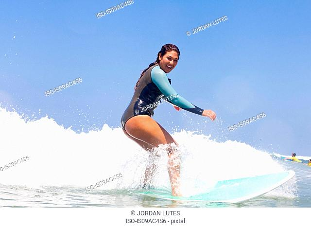 Young woman surfing, Hermosa Beach, California, USA