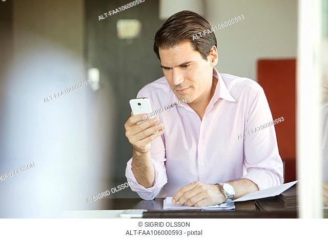 Man checking smartphone in office