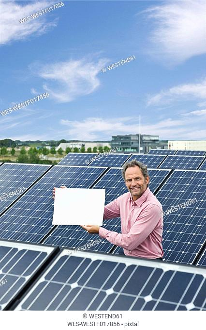 Germany, Munich, Mature man holding blank white board in solar plant, smiling, portrait