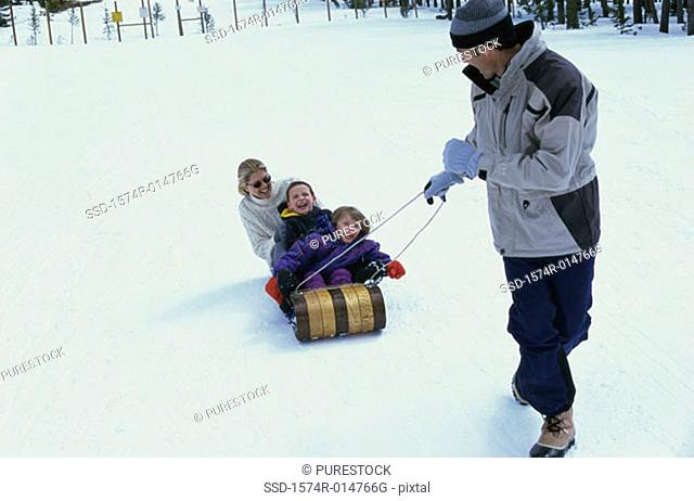 Father pulling his family on a sled