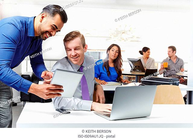 Two businessmen having discussion, looking at digital tablet, colleagues working in background