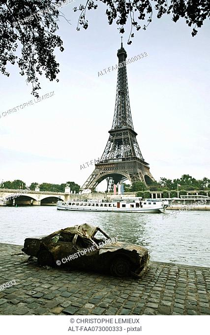 Wrecked car abandoned along Seine River near Eiffel Tower, Paris, France