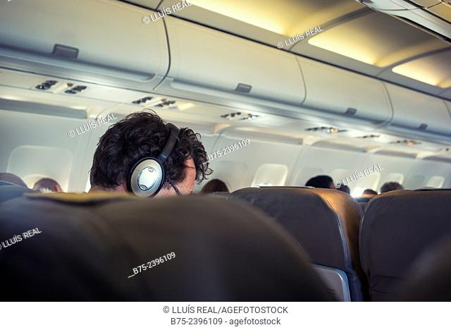 Closeup of the head of a man with headphones listening music on an airplane