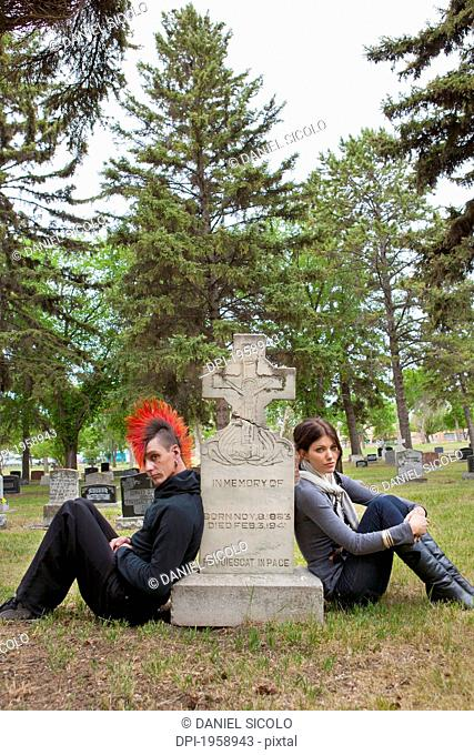 A Young Man And Young Woman Sitting By A Tombstone; Edmonton, Alberta, Canada