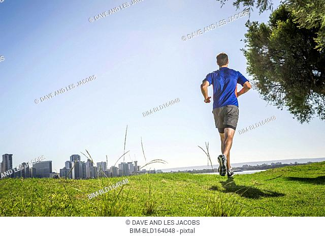 Caucasian man running on grassy hill near Perth city skyline, Western Australia, Australia