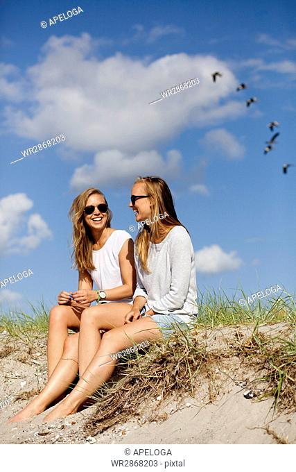 Young female friends sitting on sand at beach against sky
