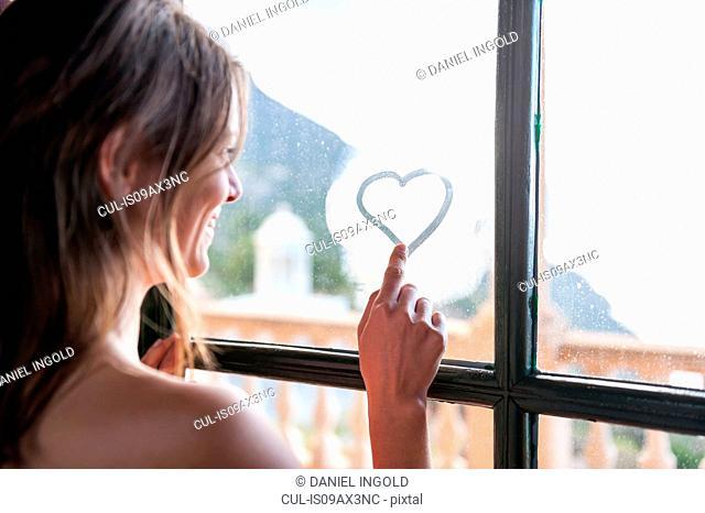 Woman drawing heart shape with finger on window, Majorca, Spain