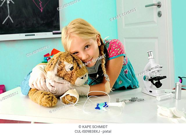 Portrait of girl pretending to be vet hugging toy tiger with intravenous drip