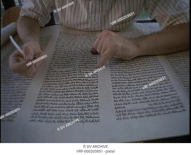 A calligrapher works on a Torah scroll