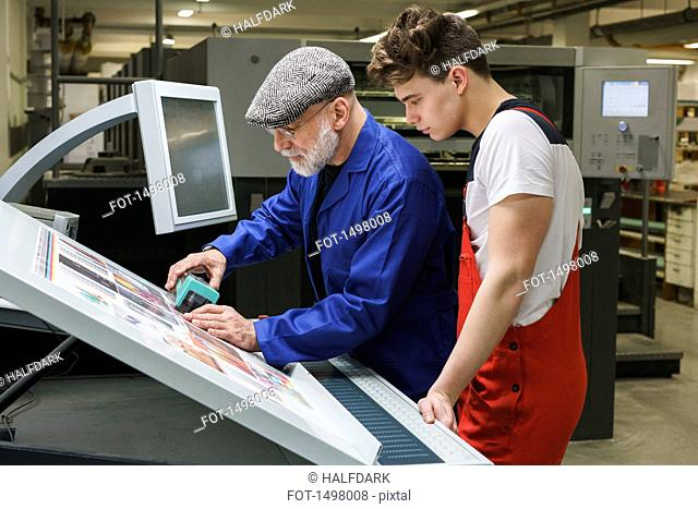 Young worker looking at mature colleague doing quality check of printout with scanner