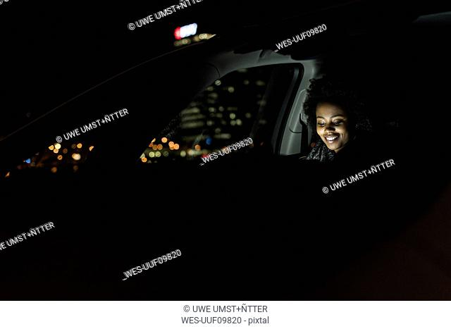 Smiling young woman sitting in a car at night using tablet