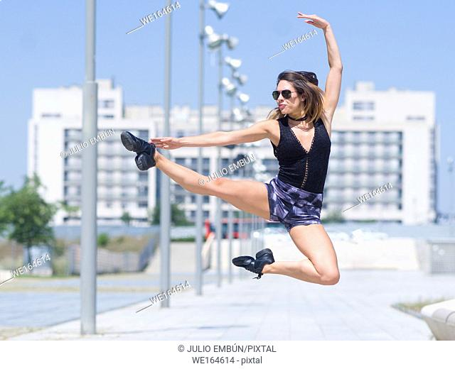 young ballerina dances and jumps on the street of a city. In Zaragoza, Aragón, Spain