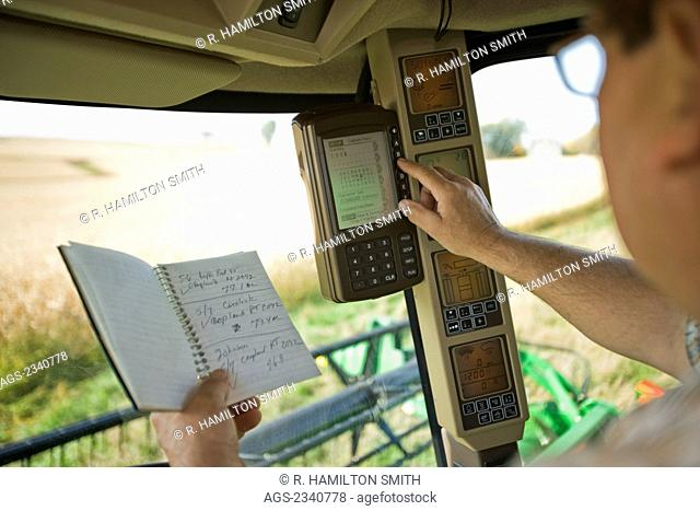 Agriculture - A farmer inputs data into the yield monitor in the cab of a combine during the soybean harvest / near Northland, Minnesota, USA