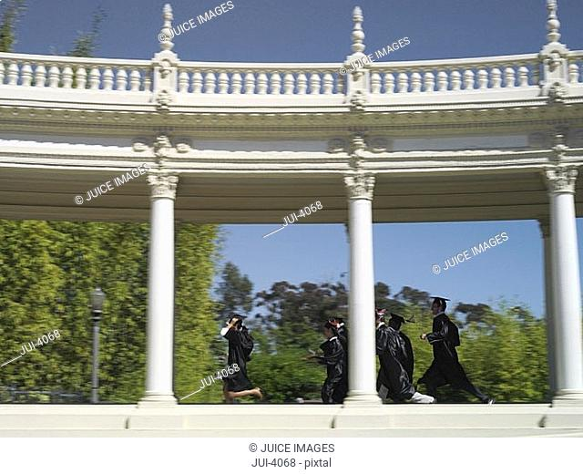 University students in graduation gowns and mortar boards walking in colonnade, side view