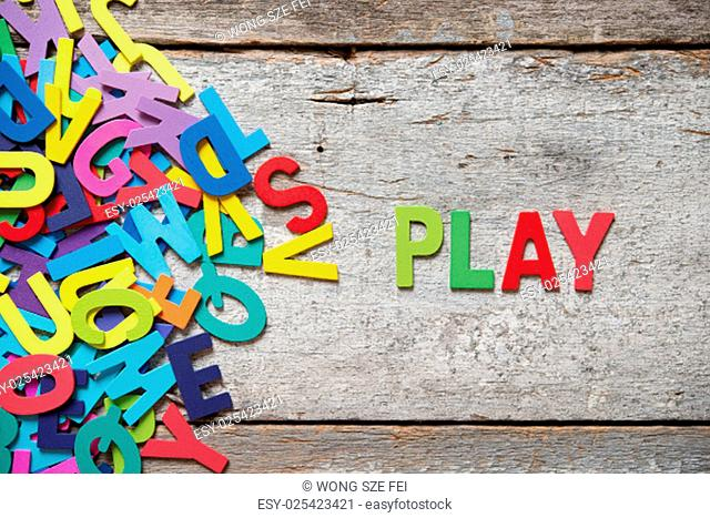 """The colorful words """"""""PLAY"""""""" made with wooden letters next to a pile of other letters over old wooden board"""