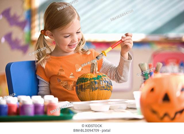 Caucasian girl painting pumpkin