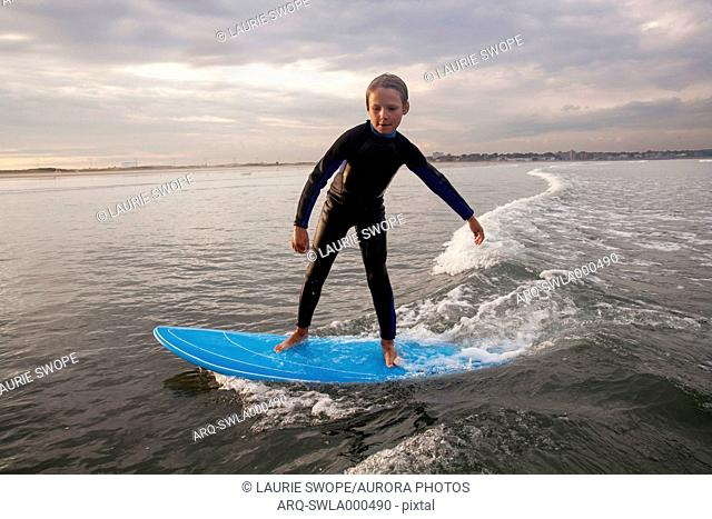 A Boy Surfs At Nahant Beach In Nahant, Massachusetts