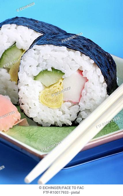 Plate of sushi with ginger and chopsticks