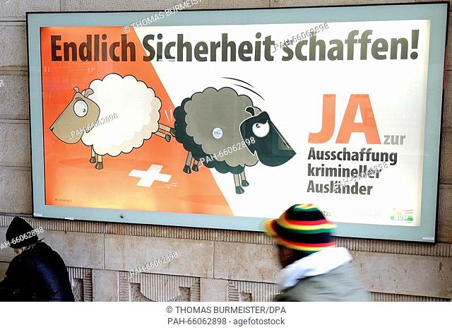 A man walking past a poster used by the Swiss People's Party (SVP) to advertise their initiative for the eviction of criminal foreigners, Basel, Switzerland