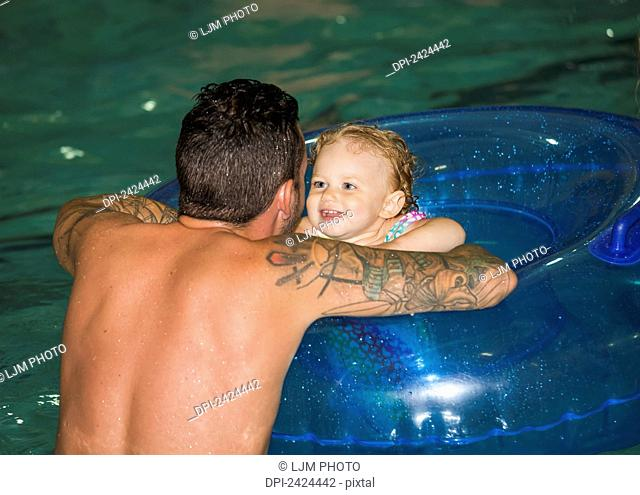 Father swimming with toddler in inflatable tube in a pool; St. Albert, Alberta, Canada