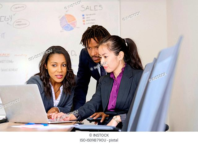 Businessman and businesswomen, in office, brainstorming, using laptop
