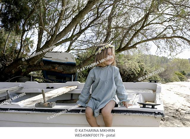 Smiling little girl wearing flowers sitting on boat on the beach