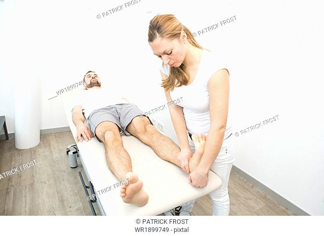Physiotherapist helping patient to do leg exercise