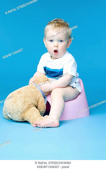 small boy sitting with teddy bear on toilet